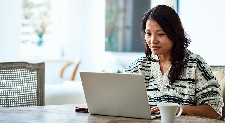 Mid adult woman in her 30s sitting at table and looking at computer, remote working, freelancer, small business